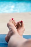 Feminine feet relaxing by the pool Stock Image