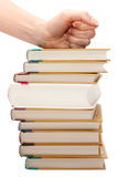 Feminine fist on pile of the books. Insulated on white background Royalty Free Stock Images