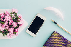 Feminine flat lay on blue background, top view of woman`s desktop with  envelope, flowers, pen,  notepad and smartpho Stock Photos