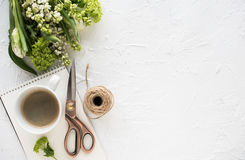 Feminine flatlay with flowers and ccoffee on white tabletop. Feminine flatlay with flowers and ccoffee on white textured tabletop, design ready arrangement Stock Photography
