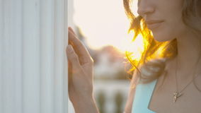 Feminine girl in the blue dress standing on the balcony near the columns at sunset stock footage