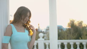 Feminine girl in the blue dress standing on the balcony near the columns at sunset stock video