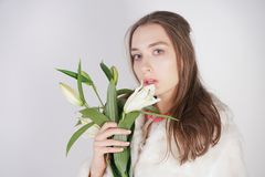 Feminine girl in a white fur coat with a branch of lilies in the background in the Studio. Isolated stock photography
