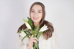 Feminine girl in a white fur coat with a branch of lilies in the background in the Studio. Isolated stock images