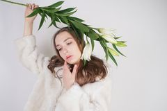 Feminine girl in a white fur coat with a branch of lilies in the background in the Studio. Isolated stock photos