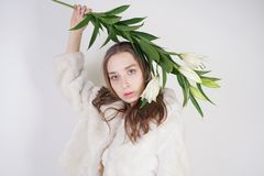 Feminine girl in a white fur coat with a branch of lilies in the background in the Studio. Isolated royalty free stock image