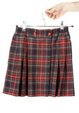 Feminine hand keeps plaid skirt Stock Photos