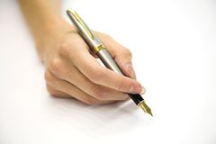 Feminine hand with pen. On white background Royalty Free Stock Image