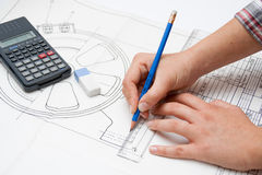 Feminine hand working on design plans. Pic stock photography