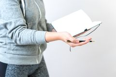 Feminine hands gesturing holding a pen and a notebook royalty free stock image