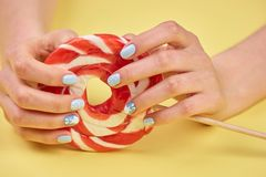Feminine hands holding bright lollipop. Royalty Free Stock Image