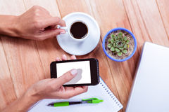 Feminine hands holding smartphone and black espresso Royalty Free Stock Photography