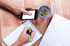 Feminine hands holding smartphone and taking notes Stock Image