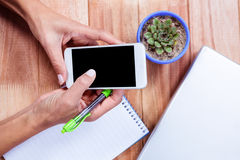 Feminine hands holding smartphone and taking notes Stock Images