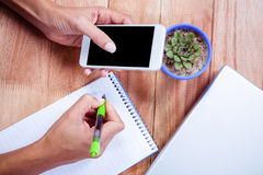 Feminine hands holding smartphone and taking notes Royalty Free Stock Photo