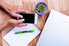 Feminine hands holding smartphone and taking notes. Overhead of feminine hands holding smartphone and taking notes Royalty Free Stock Photos