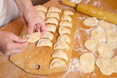 Feminine hands prepare traditional dumplings Stock Images