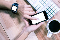 Feminine hands with smartwatch using smartphone Royalty Free Stock Photo