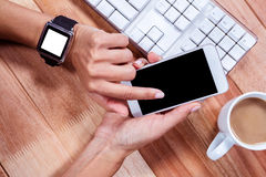 Feminine hands with smartwatch using smartphone Royalty Free Stock Photos