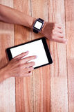 Feminine hands with smartwatch using tablet Royalty Free Stock Image
