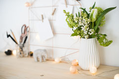 Feminine hipster office table decoration. With flowers and mood board on white wall, woman`s workplace Royalty Free Stock Photo