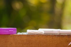 Feminine hygiene product - menstruation cotton tampon over a wooden structure with a purple thing, in a blurred Stock Image