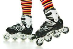 Feminine legs with roller skates Stock Photos