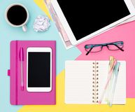 Feminine Office Desk Working Space Flat Lay. Top view photo of workspace. notepad and woman fashion magazines on pastel background royalty free stock images