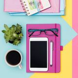 Office Desk Working Space Flat Lay. Top view photo of workspace with smartphone, coffee, notepad and woman fashion magazines. Feminine Office Desk Working Space stock photo