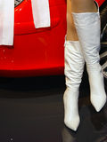 Feminine pair of legs. A feminine pair of legs clad in high, white boots, appears next to a bright, red, car Stock Images