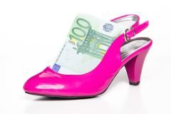 Feminine pink high-heeled shoe and 100 euro Stock Photo