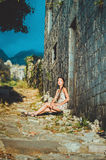 Feminine portrait of young romantic woman sitting on oldest stone road in Old Bar, Montenegro. Summer travelling Stock Image