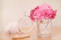 Feminine romantic setting on the table with Pink Oleander flower. S in the glass, parfume and cookies, textured image Stock Photos