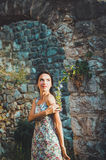 Feminine romantic woman posing in Stari Bar old fortress, Montenegro. Tanned female with long hair, red lips and Royalty Free Stock Photos