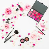 Feminine round desk with cosmetic and pink flowers on white background. Flat lay, top view. Beauty frame for woman Stock Photography