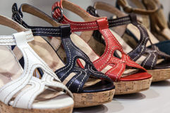 Feminine Sandals. A row of colorful  leather feminine sandals on a shelf of a shoes store Royalty Free Stock Photo