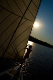 Feminine silhouette on a yacht. In the background of the sunset sky Stock Photos