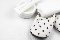 Feminine slippers and toiletry. Pair of feminine slippers with white and black polka dot decor and toiletry on white carpet Royalty Free Stock Photos