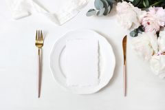 Feminine wedding, birthday desktop mock-up scene. Porcelain plate, blank craft paper greeting cards, silk ribbon, golden. Cutlery, eucalyptus, peony flowers royalty free stock photos