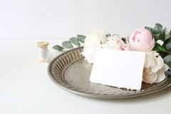 Feminine wedding or birthday table composition with floral bouquet. White and pink peonies flowers and eucalyptus. Branches on old vintage silver tray. Craft stock image