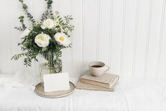 Feminine wedding or birthday table mockup scene with floral bouquet. White peonies, tanacetum flowers, eucalyptus