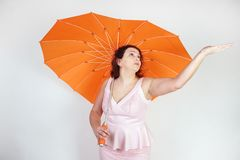 Feminine woman with plus size body in pink dress with orange big heart shaped umbrella posing on white background in Studio. Isolated royalty free stock photo