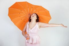 Feminine woman with plus size body in pink dress with orange big heart shaped umbrella posing on white background in Studio. Isolated stock images