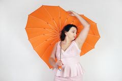 Feminine woman with plus size body in pink dress with orange big heart shaped umbrella posing on white background in Studio. Isolated stock photo