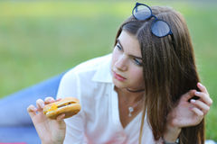 Feminine working lying in glasses in the park and food snack. Girl lying on the nature and eateth fast food. student working in the park and eat Stock Photo