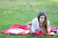 Feminine working lying in glasses in the park and food snack. Girl lying on the nature and eateth fast food. student working in the park and eat Stock Photos