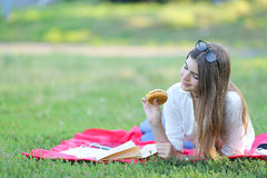 Feminine working lying in glasses in the park and food snack. Girl lying on the nature and eateth fast food. student working in the park and eat Royalty Free Stock Photo