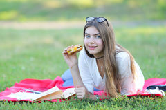 Feminine working lying in glasses in the park and food snack. Girl lying on the nature and eateth fast food. student working in the park and eat Royalty Free Stock Photography