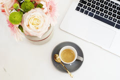 Feminine workplace concept in flat lay style with laptop, coffee. Flowers on white marble background. Top view Royalty Free Stock Photos