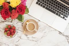 Feminine workplace concept. Freelance fashion comfortable femininity workspace in flat lay style with laptop, coffee cup, flowers royalty free stock photography